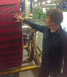 Eliot Orton, Proprietor, inspecting Portuguese flannel in Red Stewart Plaid