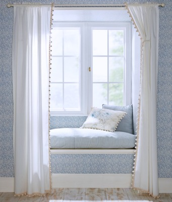 Classic ball fringe curtains create a private reading nook
