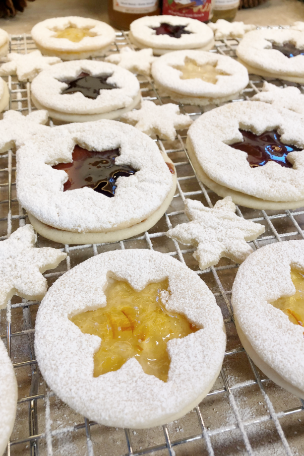 snowflake cookies filled with jam and covered with powdered sugar, still cooling on the trays