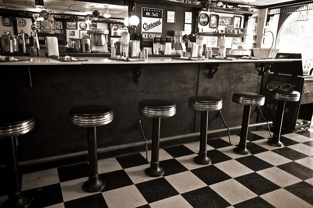 old fashioned soda shop counter with stools and signs