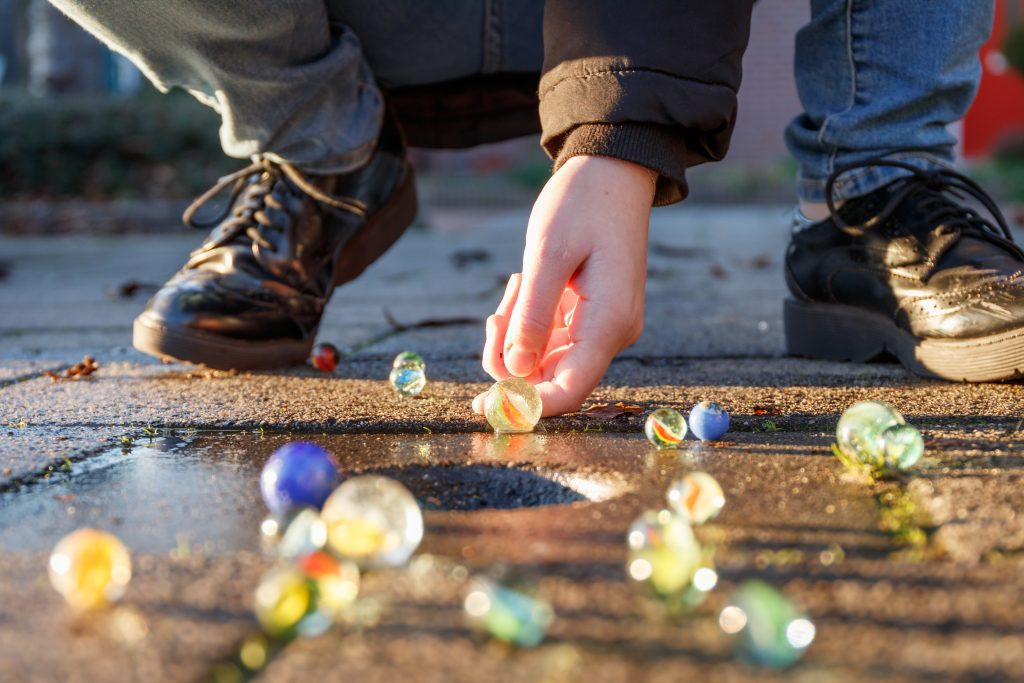 A young person crouches to shoot their marble into the ring.